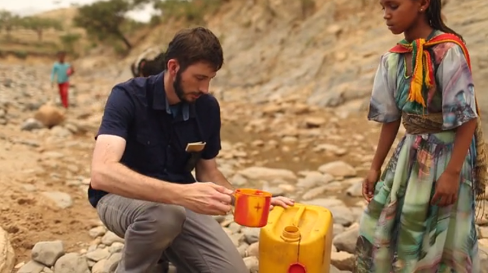 Tyler Riewer collects water with a 14-year-old girl. (Photo credit: charity: water) http://www.charitywater.org/journey